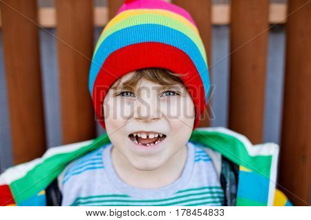 outdoor fashion portrait of adorable little kid boy wearing colorful clothes. spring fashion for boys and children. boy with tooth gap