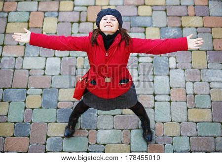 Happy girl. Pretty young smiling woman in a red jacket and beret is standing with arms outstretched and looking up.