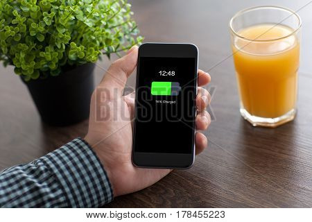 man hand holding phone with charged battery screen on desk in office