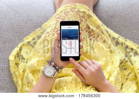 woman in yellow dress with jewelry holding phone with debit card app touch pay