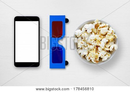 Smartphone 3d anaglyph glasses and popcorn in bowl on table
