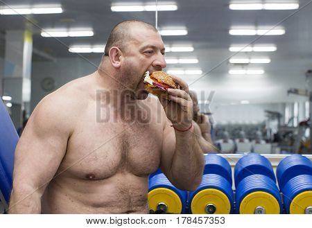 A big fat hungry man eats a hamburger with meat and cheese in the gym