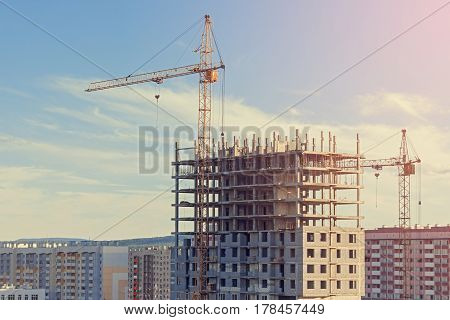 The construction of the building with a construction crane at sunset.