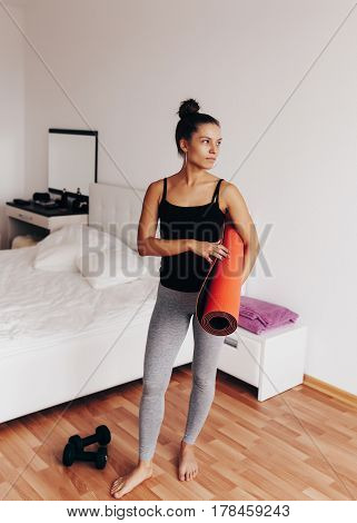 Happy attractive young woman holds in hands red yoga or fitness mat after working out at home in living room. Healthy life, keep fit concepts.