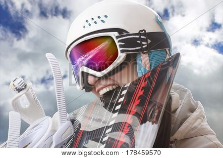 Young girl snowboarder in helmet and goggles bites snowboard.