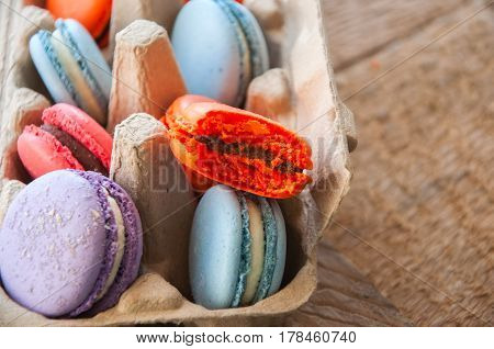 Mix Of Colorful Macarons In A Craft Paper Egg Container On A Wooden Background