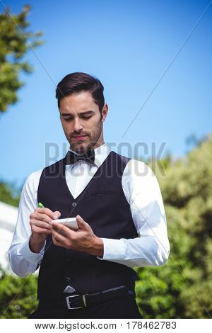 Handsome waiter writing the order outside