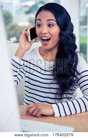 Surprised Asian woman on phone call in office