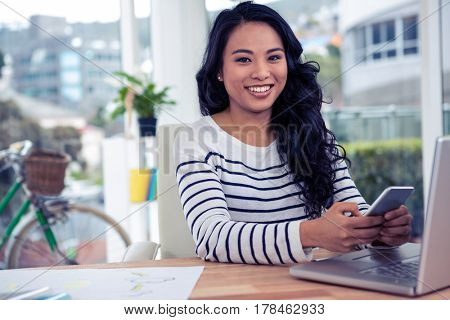 Smiling Asian woman using smartphone and laptop in office looking at the camera