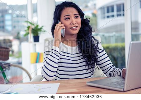 Pretty Asian woman on phone call in office