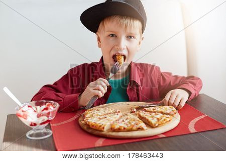 Sweet adorable child boy in stylish cap and red shirt eating pizza and ice-cream at a restaurant. Fashion little boy having breakfast at cafe. People and lifestyle concept.