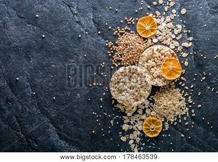 Round Crisp On A Black Stone Background. Rice Grains, Oatmeal Flakes And Buckwheat Series.