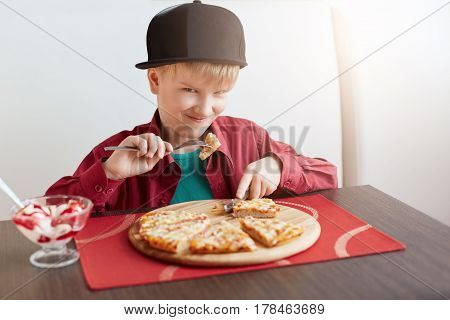 A portrait of handsome child male dressed in stylish red shirt and black cap eating pizza and ice-cream being in cosy cafe looking with deligtment into camera. A little boy having lunch in restaurant