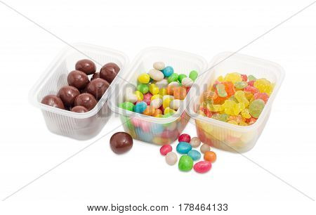Malted milk balls covered chocolate varicolored sugar candies and candies made of the sugar glazed raisins and called sea pebbles in different small plastic containers on a light background