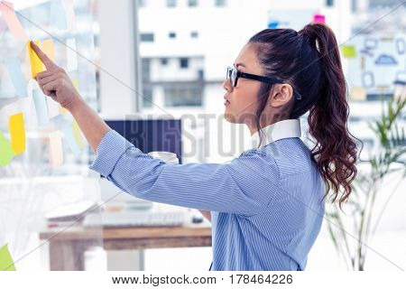 Businesswoman holding disposable cup and looking at wall with notes in office