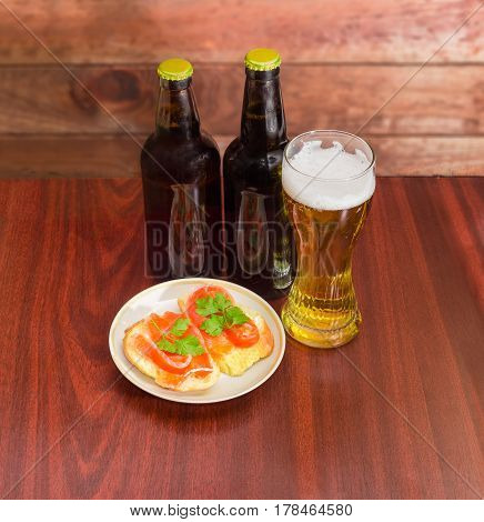 Two different bottles and glass of the lager beer and two sandwiches made with a salted trout on the saucer on the dark red wooden table