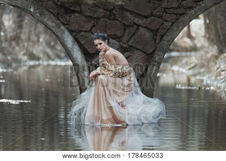 Atmospheric Outdoor Portrait Of Sensual Young Woman Wearing Elegant Dress Sitting Under The Bridge O