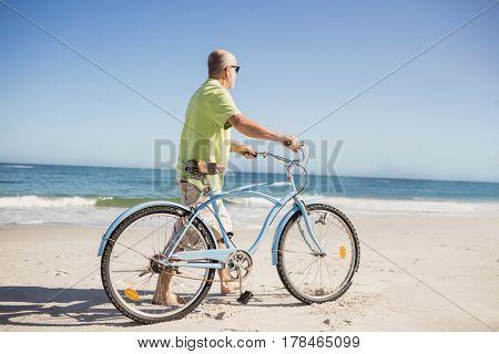 Smiling senior man with bike on the beach