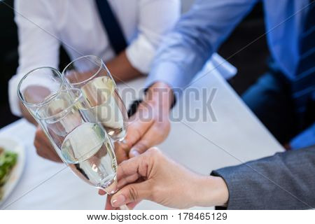 Close-up of hands toasting with champagne