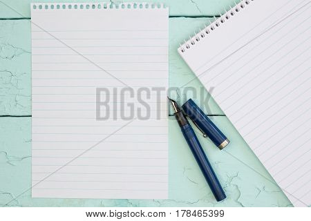 Blank note pad paper, with note pad, fountain pen on rustic blue deck table