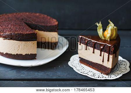 Delicious cake with chocolate sauce, fruit and plate with slace of this cake on lace napkin
