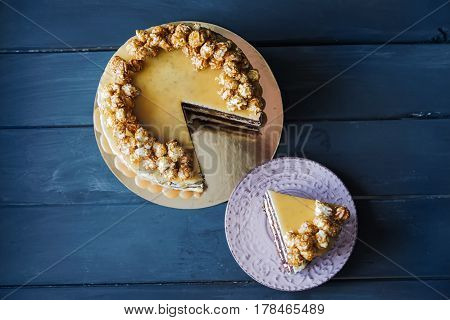 Delicious cake with caramel popcorn and caramel sauce and plate with slace of this cake, top view