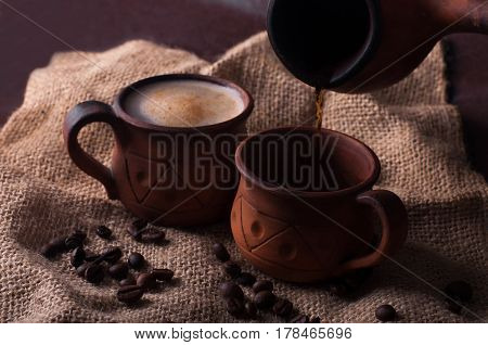Coffee morning coffee beans concept - coffe in earthenware cup and coffe beans on brown background