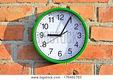 Green Wall Clock Hanging On A Brick Wall