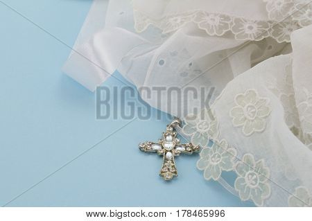 Vintage lace christening gown with Christian silver and crystal cross pendant isolated on light blue background