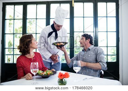 Upset man showing food to chef in restaurant