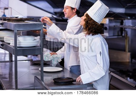 Two chefs working at order station in a restaurant kitchen