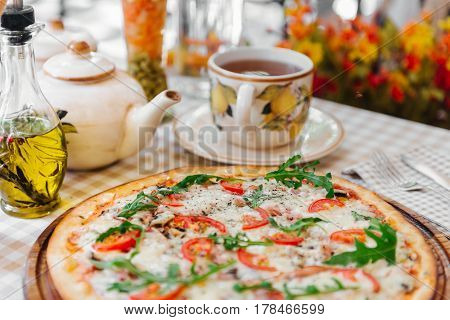 Pizza with cheese, tomato and meat, with cup of tee on served table with plaid tablecloth