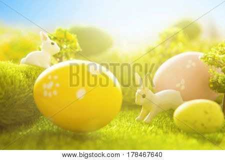 Rabbits With Easter Eggs On Green Meadow Over Sundown. Cute Little Easter Bunny On Spring Flowers An