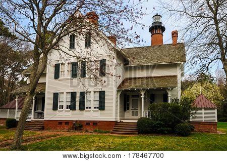 A lighthouse keeper's home by a brick lighthouse