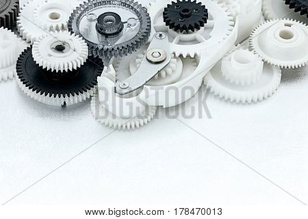 White And Black Plastic Gears On Scratched Metal Background