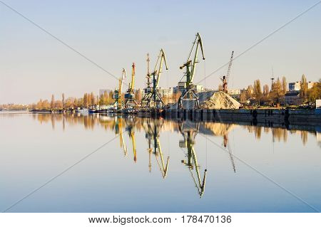 Row of cargo port cranes reflected in calm river water