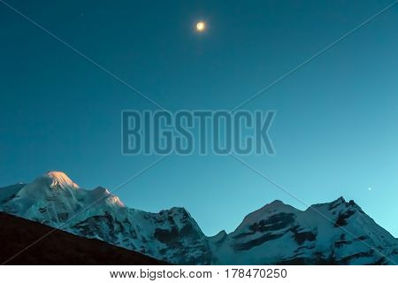 Evening high Altitude Mountain Range View with Sunset between Rocks and young Moon rising