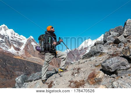 One adult Mountain Climber with Backpacks Gear and high Altitude Clothing walking up on rocky Ridge with Himalaya Summits on Background