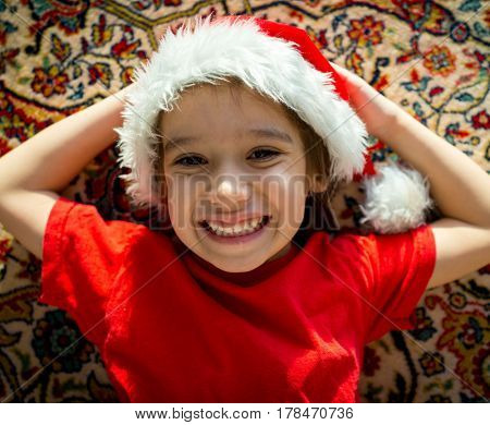 Santa cute kid on carpet at home smiling