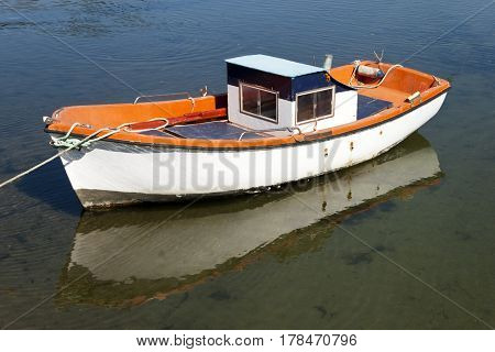 Old white and orange small boat in A Foz marsh in A Ramallosa Nigran Pontevedra Galicia Spain.