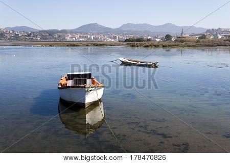 Old boats in A Foz marsh in A Ramallosa Nigran Pontevedra Galicia. Sabaris and Galineiro mountain range at background.