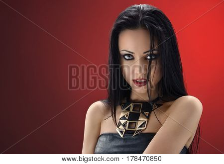 Fire in her eyes. Studio shot of a beautiful young brunette woman wearing professional makeup and black leather dress posing on red background copyspace sexuality seduction concept