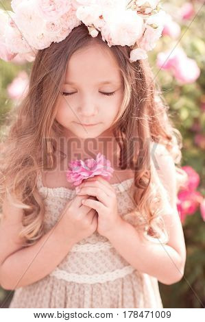 Smiling baby girl 4-5 year old with eyes closed holding rose flower outdoors. Summer time.