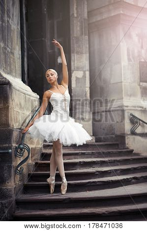 Catching last sun beams. Portrait of a ballerina performing outdoors near an old building