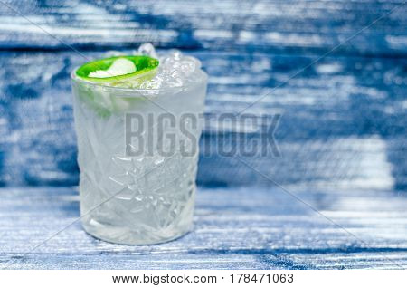 Transparent glass with tonic with ice and lime on a blue denim background