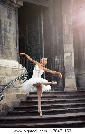 She went looking for inspiration. Full length portrait of a ballerina dancing gracefully near an old house