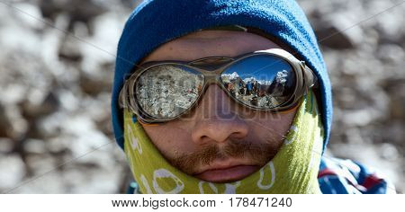 Close Up Portrait of Mountain Climber in warm Cap Head Bandana and protective Sunglasses