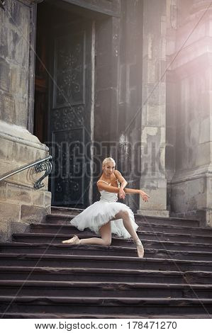 Love to see her dance. Soft focus shot of a ballerina posing on her knee standing on the stairs of an old building