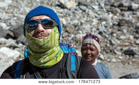 Portrait of caucasian Mountain Climber n warm Cap Head Bandana and protective Sunglasses and nepalese professional high altitude Guide