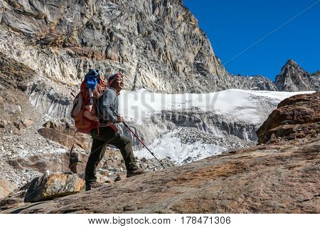 Iconic Portrait of Nepalese professional Mountain Guide staying on Rock and looking up at high Altitude Summits carrying Backpack with alpine climbing Gear poster
